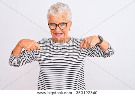 Senior grey-haired woman wearing striped navy t-shirt glasses over isolated white background looking confident with smile on face, pointing oneself with fingers proud and happy.