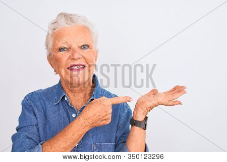 Senior grey-haired woman wearing casual denim shirt standing over isolated white background very happy pointing with hand and finger