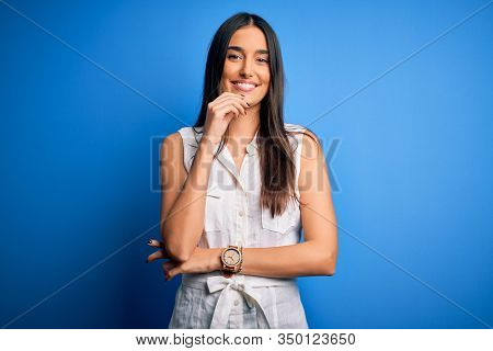 Young beautiful brunette woman wearing casual dress over isolated blue background looking confident at the camera with smile with crossed arms and hand raised on chin. Thinking positive.