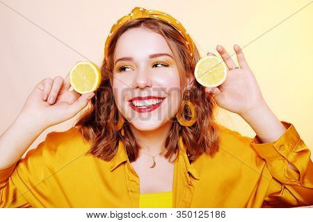 Beautiful Girl, Yellow Make-up, Bright Colors. Girl Holds Lemons Near Her Face, Smiling. Facial Mask