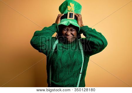 Plus size african american woman with braids wearing green hat with clover on st patricks day suffering from headache desperate and stressed because pain and migraine. Hands on head.