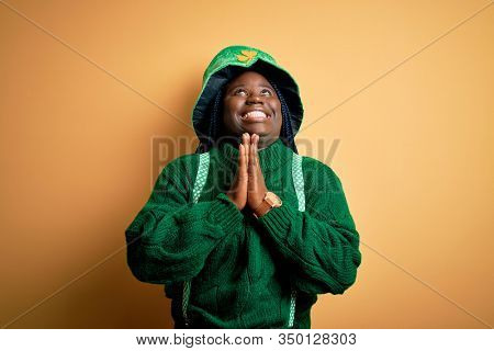 Plus size african american woman with braids wearing green hat with clover on st patricks day begging and praying with hands together with hope expression on face very emotional and worried. Begging.