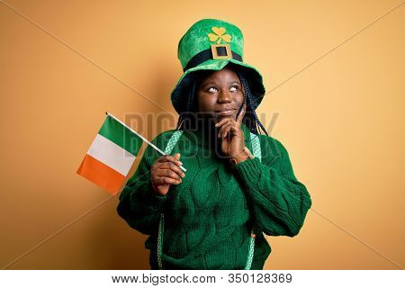 Plus size african american woman wearing green hat holding irish flag on saint patricks day serious face thinking about question, very confused idea