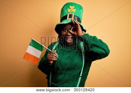Plus size african american woman wearing green hat holding irish flag on saint patricks day with happy face smiling doing ok sign with hand on eye looking through fingers