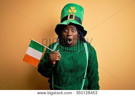 Plus size african american woman wearing green hat holding irish flag on saint patricks day scared in shock with a surprise face, afraid and excited with fear expression