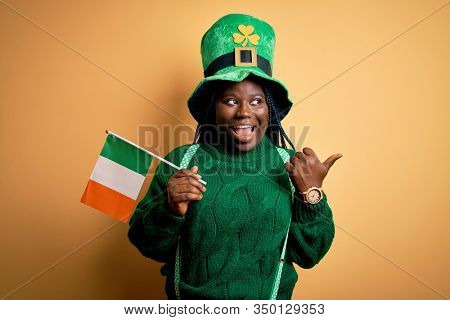 Plus size african american woman wearing green hat holding irish flag on saint patricks day pointing and showing with thumb up to the side with happy face smiling