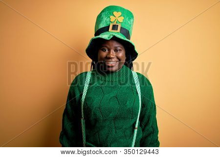 Plus size african american woman with braids wearing green hat with clover on st patricks day with a happy and cool smile on face. Lucky person.