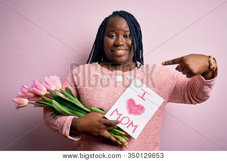 Plus size african american woman holding love mom message and tulips on mothers day with surprise face pointing finger to himself