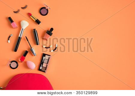 Red Makeup Bag And Cosmetic Products Spilling Out On To Pastel Peach Color Background. Flat Lay, Top