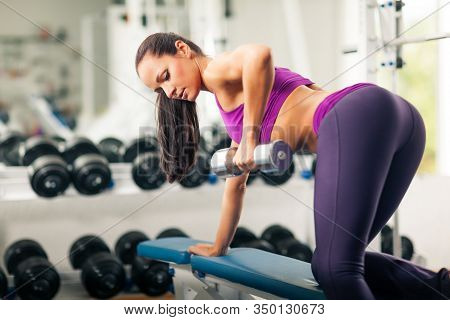 Side View Of Sporty Lady With Well-shaped Body Doing Exercise With Dumbbell In Gym. Beautiful Athlet