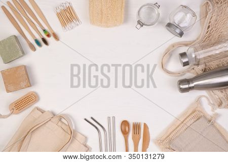Zero waste eco friendly reusable objects such as reusable linen shopping bags, glass jars and wooden toothbrushes, top view with copy space