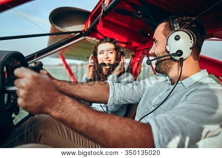 Cool Young Pilot And Happy Young Woman Sitting In Cabin Of Private Airplane To Fly On A Vacation Thi