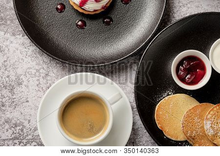 Cup Of Americano Coffee With Pancakes And Sour Cream Cake For Breakfast. A Cup Of Black Coffee In A