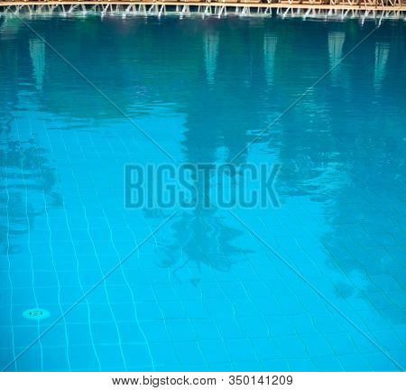 Outdoor Pool. Through The Water You Can See The Bottom Of The Pool. Palm Trees And Sun Umbrellas Are