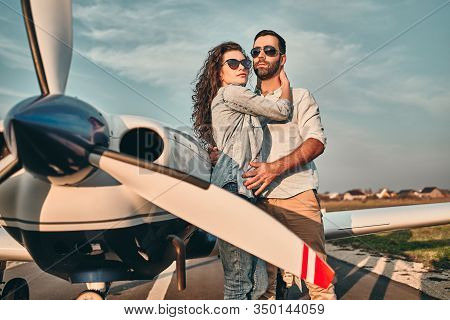 Beautiful And Happy Young Couple Posing In Front Of An Old Retro Private Propeler Airplane