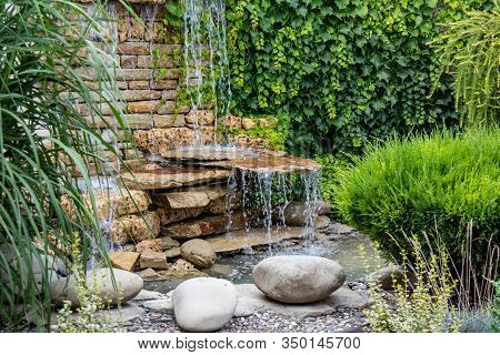 A Small Decorative Waterfall In The Park Or In The Garden. Landscape Design