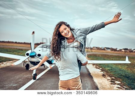 Happy Loving Couple Of Tourist Have Fun In The Airport And Make Airplane.
