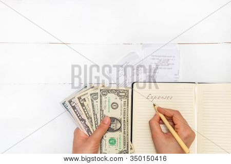Expenses Planning Concept. Top View Of Receipts, Woman Holding Pen And Cash And Writing Words Expens