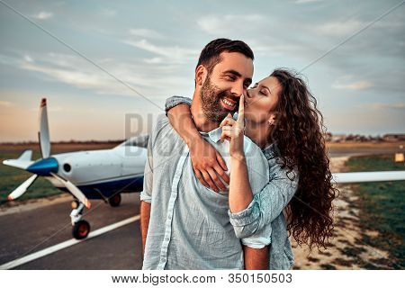 Young Handsome Man Pilot Is Standing Near Small Private Plane With His Beautiful Young Woman.