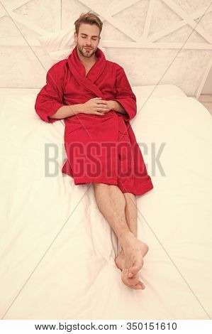 Knowing How To Relax. Handsome Man Lying In Bed To Relax After Bath. Sleepy Guy In Red Bathrobe Taki