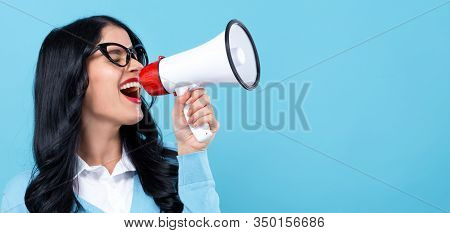 Young Woman With A Megaphone On A Blue Background