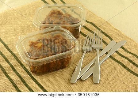 Two Take Out Deli Boneless Chicken Lunches In Plastic Containers With Knives And Forks On Place Mat