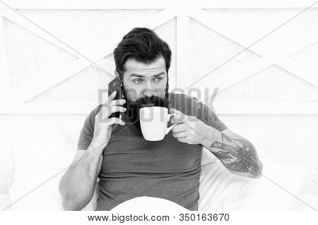 Bearded Man Using Mobile Technology In Bed. Handsome Guy Talking On Phone And Drinking Coffee At Hom