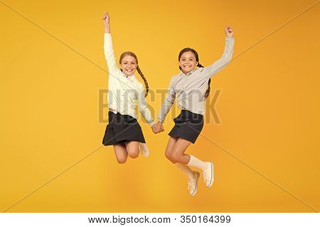 Cuties In Mid Air. Active Children Jumping High On Yellow Background. Happy Girls Enjoying Active Li