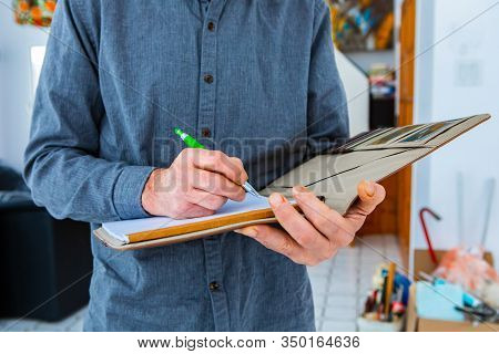 A Close Up And Selective Focus Shot Of A Notebook Held By Inspectors Hands With A Green Pen As He Ta