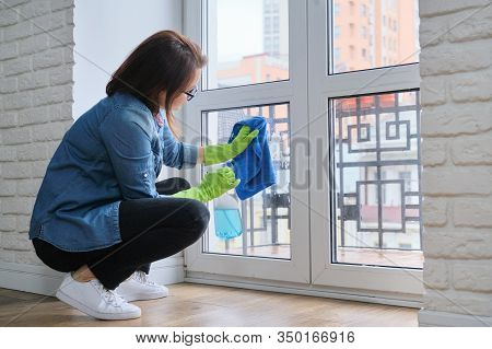 Mature Woman Cleaning Windows At Home In Spring, Woman With Detergent Spray Bottle With Rag In Glove