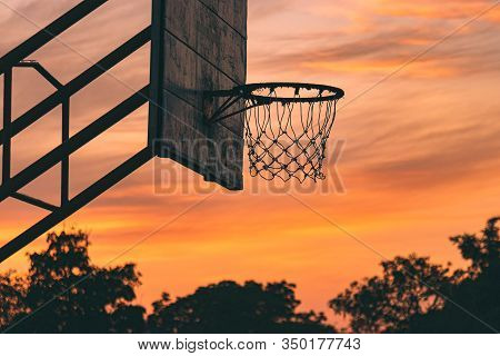Silhouette Of Old Outdoor Basketball Court With Dramatic Sky In The Sunrise Morning