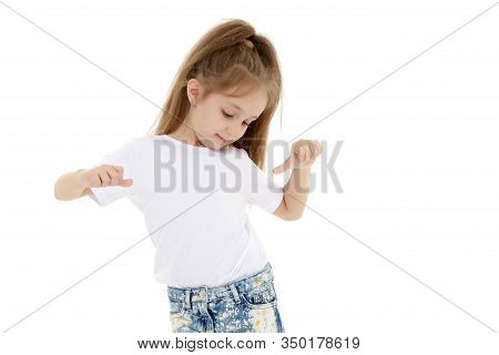 A Beautiful Little Girl In An Empty White T-shirt Points To Herself. The Concept Of Design Of T-shir