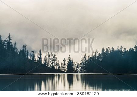 Silhouettes Of Pointy Fir Tops On Hillside Along Mountain Lake In Dense Fog. Reflection Of Coniferou