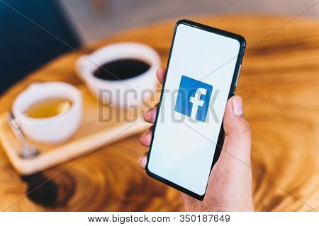 Chiang Mai, Thailand - Jan.18,2020: Man Holding Xiaomi Mi Mix3 With Facebook App On Wooden Table At