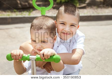 Lovely Small Smiling Infant Boy Hugging His Brother Sitting On A Green Trike In The Park. Concept Of