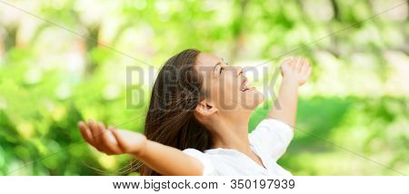 Happy clean air Asian woman breathing in fresh outdoor nature forest panoramic banner for allergy free pollen allergies.