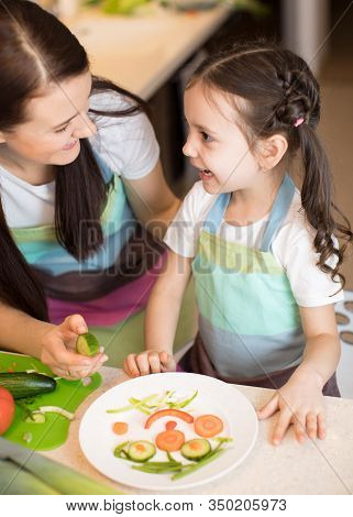 Happy Mother And Her Little Daughter Enjoy Making Healthy Meal Together At Their Kitchen