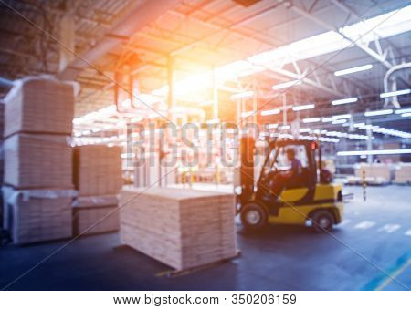 Bloored Background Of Forklift Loader In Storage Warehouse Ship Yard.