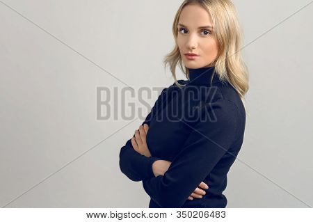 Studio Portrait Of A Beautiful Young Woman With Blond Hair Looking At Camera With Confident Attitude