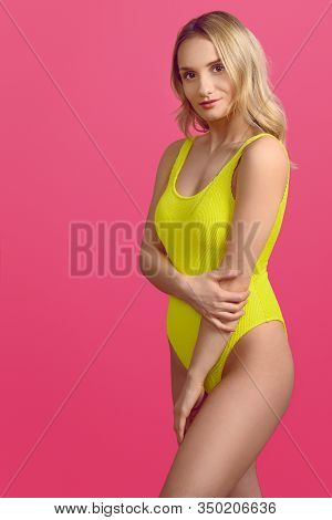 Beautiful Sexy Young Woman In Yellow Swimsuit Plying With Her Long Blond Hair As She Gives The Camer