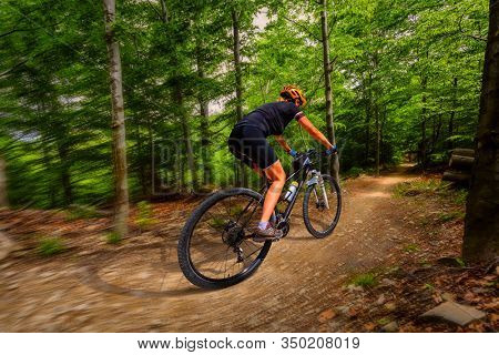 Motion blur picture of cycling woman riding on bike in autumn mountains forest landscape. Woman ride MTB flow trail track. Outdoor sport activity.