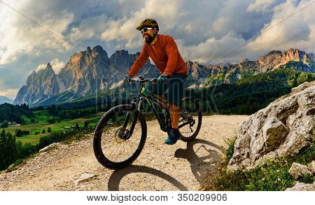 Tourist cycling in Cortina d'Ampezzo, stunning rocky mountains on the background. Man riding MTB enduro flow trail. South Tyrol province of Italy, Dolomites.