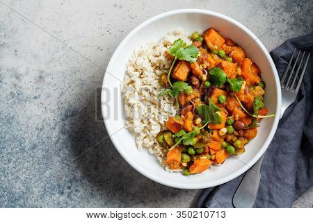 Vegan Curry With Rice In A White Bowl. Curry With Sweet Potato, Peas And Beans In A Plate With Rice.