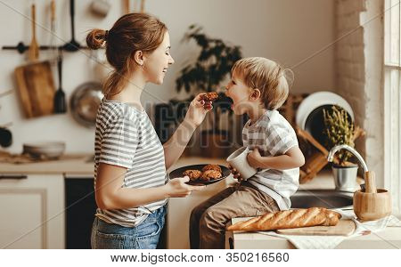 Preparation Of A Family Breakfast. Mother And Child Son Cut Bread And Eat Cookies With Milk In Morni