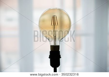 Light Bulb Close Up. Close Up Image Of Light Bulb. Light Bulb Background. Light Bulb On Blurred Back