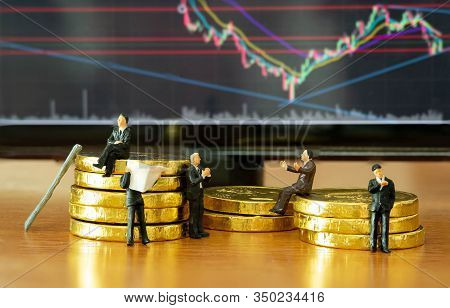 The Miniature Figure A Group Of Business Men Sitting On Top Of Pile Stack Of Golden Coins And Some S