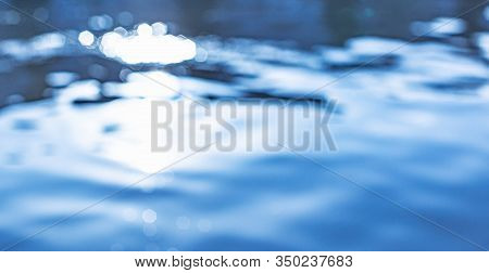 Soft Focus Bokeh Light Effects Over A Blue Water Background With Lens Flare.