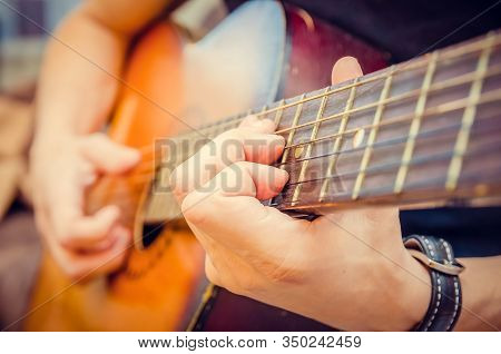 Close-up Of A Guitarist's Hand On An Acoustic Guitar. Guitar Player's Hand On The Fretboard Of An Ac