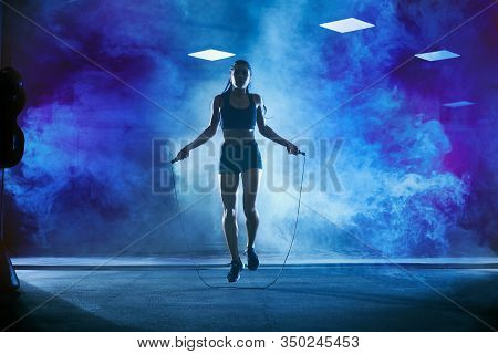Front View Of Pretty Female Bodybuilder In Sport Suit With Perfect Body Using Skipping Rope In Gym.