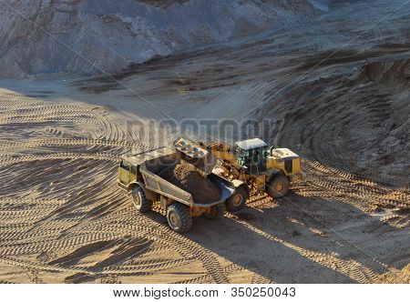 Wheel Loader Loads Sand Into Heavy Mining Dump Truck At The Opencast Mining Quarry. Heavy Machinery